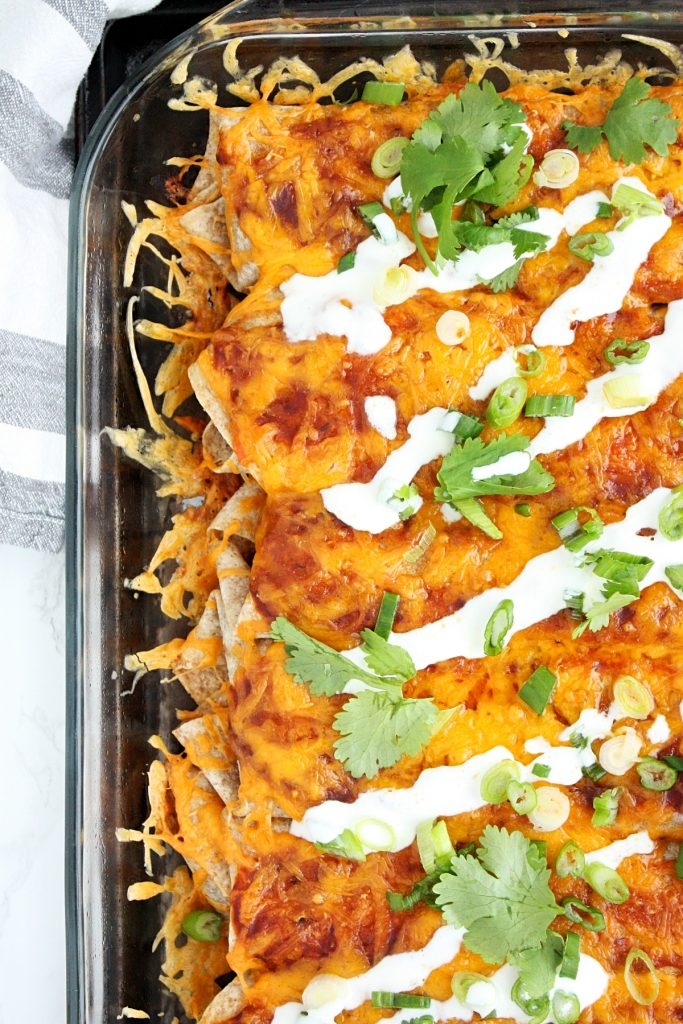 Veggie Enchiladas with Quinoa and Black Beans || This hearty vegetarian main is loaded with quinoa, spinach, black beans, and spices, topped with an easy homemade enchilada sauce and cheddar.
