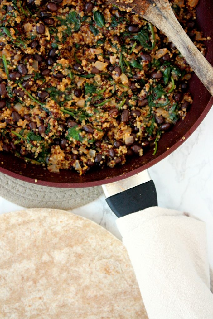 Cooked quinoa filling with spinach and black beans - ready to fill those tortillas. #mondaysundaykitchen