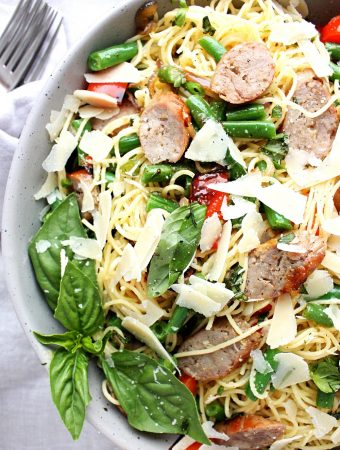 This light and easy pasta with grilled Italian sausages and red peppers is lightly dressed in lemon and olive oil and finished off with fresh basil, crunchy garden green beans, and parmesan.