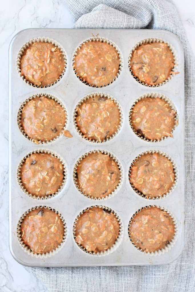 Muffin tins filled with carrot cake muffin batter.