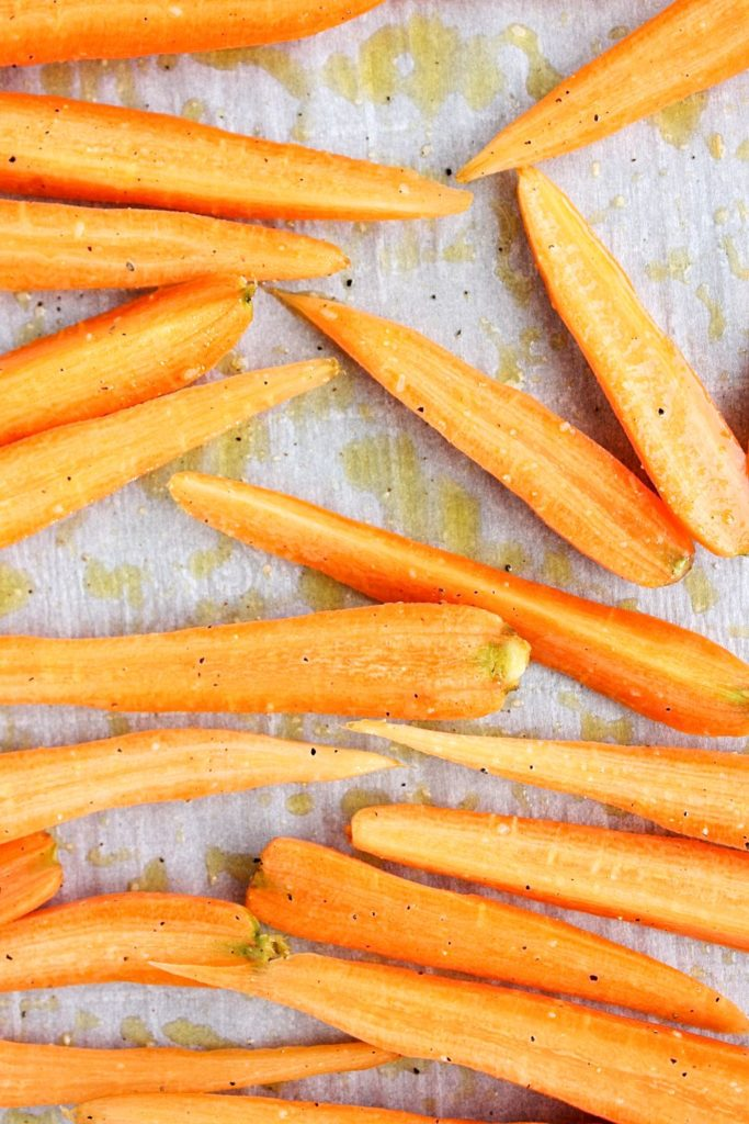 Carrots drizzled with olive oil, salt and pepper and ready for roasting.