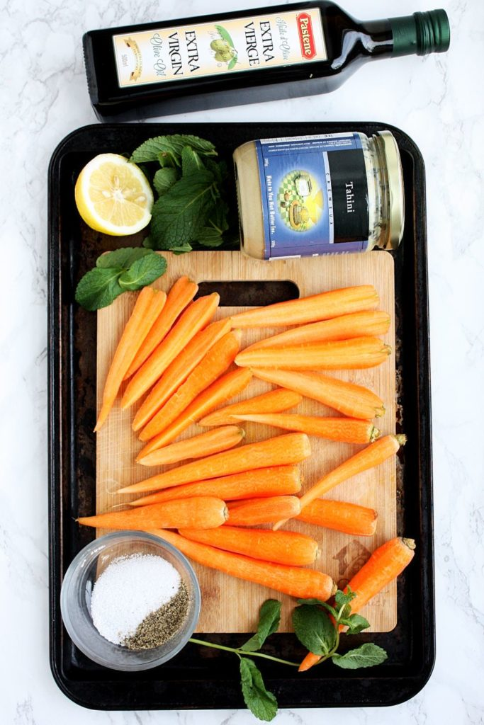 Ingredients to make oven roasted carrots with tahini dressing.