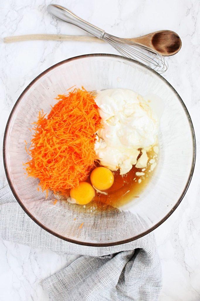 Mixing bowl with wet ingredients: eggs, milk/yogurt, carrots, honey, oil.