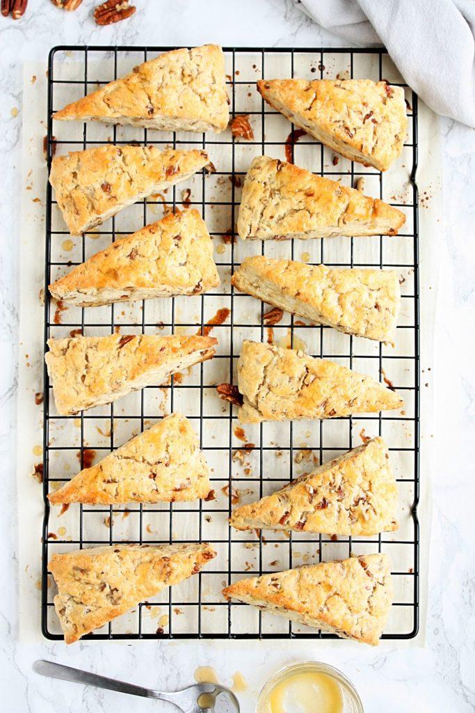 A dozen maple pecan scones on a cooling rack
