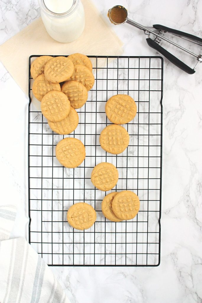 Peanut Butter Shortbread Cookies on a baking rack with a bottle of milk and a cookie scoop