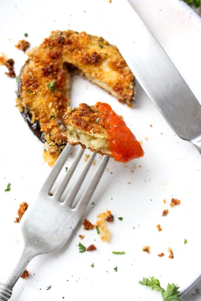 A bit of crispy eggplant dipped in marinara on a fork.
