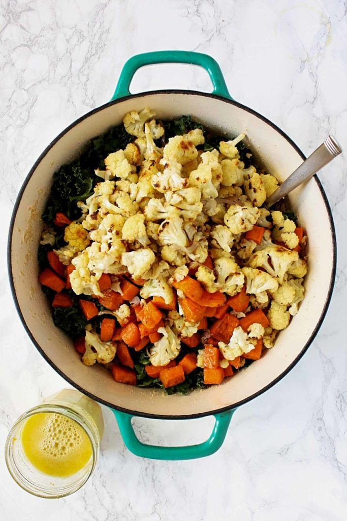 Pot of couscous topped with roasted sweet potatoes and cauliflower and a citrus dressing in a mason jar beside the pot.