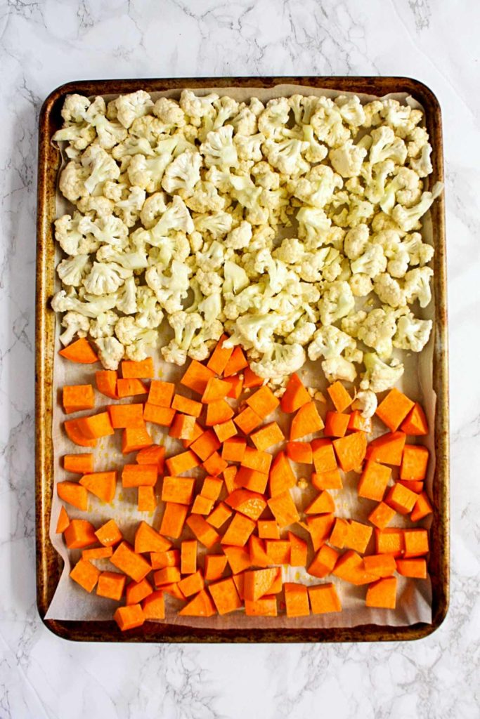 Chopped sweet potatoes and cauliflower florets on a parchment lined baking sheet, ready for roasting.
