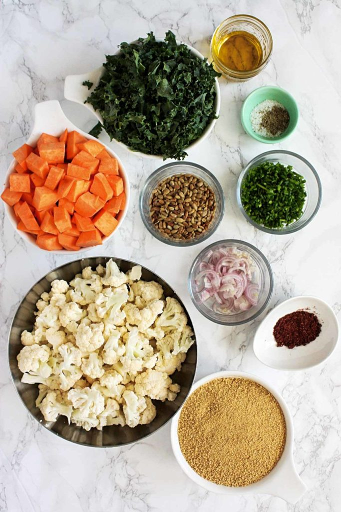 Couscous salad ingredients: whole wheat couscous, chopped sweet potatoes, cauliflower florets, chopped kale, sliced shallots, chopped chives, sunflower seeds, olive oil, salt and pepper, and sumac.