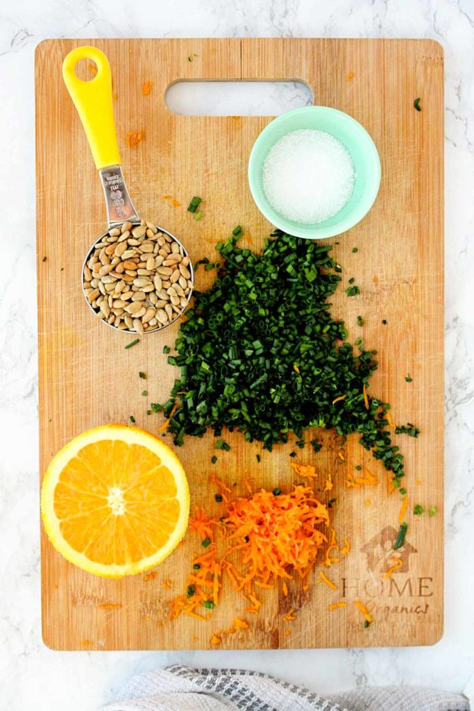 Couscous salad ingredients on a wooden cutting board: grated orange zest, sunflower seeds, chopped chives, and kosher salt.